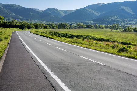 roadway: Roadway in green plateau surrounded by hills Stock Photo