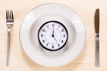 plato del buen comer: Clock on a white plate with fork ant knife Foto de archivo