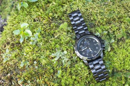 cronografo: reloj cronógrafo negro en un musgo verde brillante