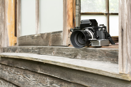 slant: Slant view of old camera and exposure meter on windowsill of wooden building