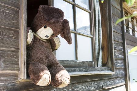 slant: Slant view of old stuffed bear on windowsill of wooden building Stock Photo