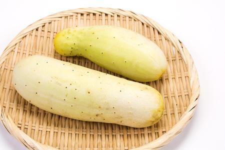 slight: Two slight green fat cucumbers on a bamboo sieve