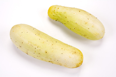 slight: Two slight green fat cucumbers on a white background Stock Photo