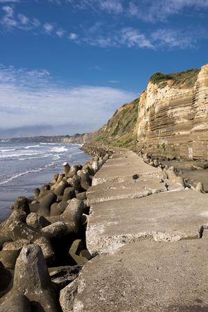 해변 tetrapots 및 수직 컴포지션에서 푸른 하늘 아래 절벽 스톡 콘텐츠
