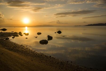 Evening calm sea and sandy beach under sky in Ishigaki island