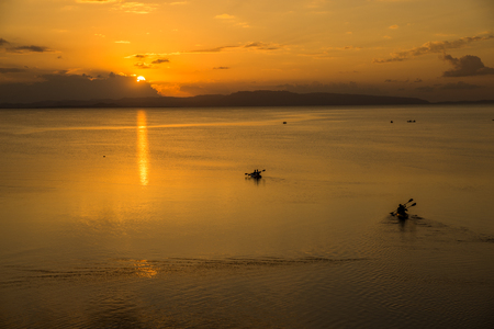 Evening orange sea on canoe silhouettes in Ishigaki island