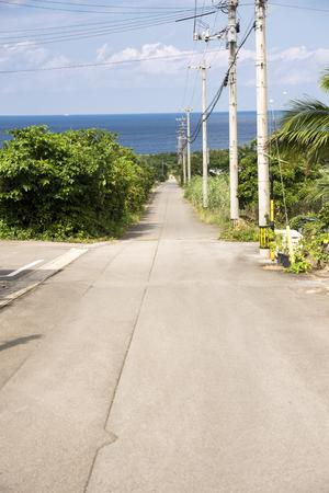 Country road leading to a sea beside telegraph poles in Ishigaki island Stock Photo
