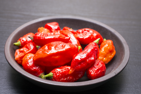 primary product: Several red Bhut Jolokia fruit on earthen round plate