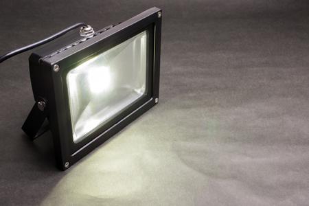 One LED floodlight emitting on dark paper Фото со стока