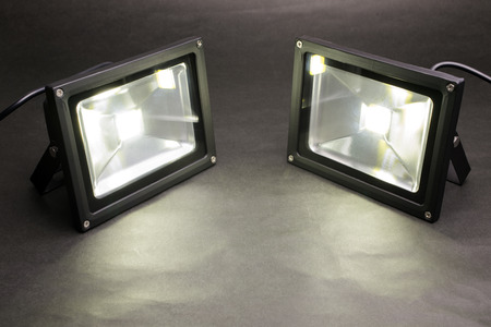 Two LED floodlights emitting on dark paper