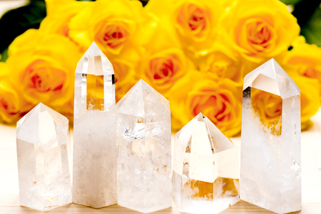 obelisk stone: Lined five obelisk rock crystals in front of yellow rose flowers Stock Photo