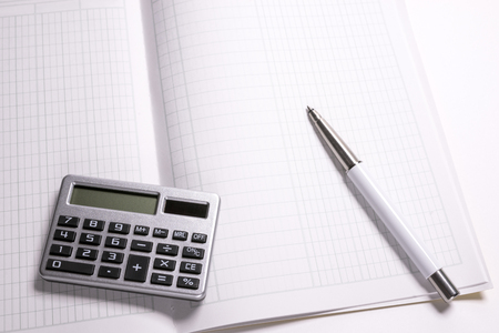 Small calculator and ballpoint pen on a account book Stock Photo