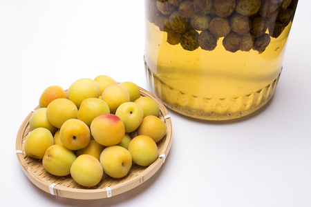 Yellow japanese apricot fruit on a bamboo sieve in front of bottled ume liquor Banco de Imagens