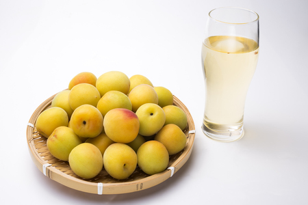 Yellow japanese apricot fruit on a bamboo sieve in front of ume liquor with glass 스톡 콘텐츠