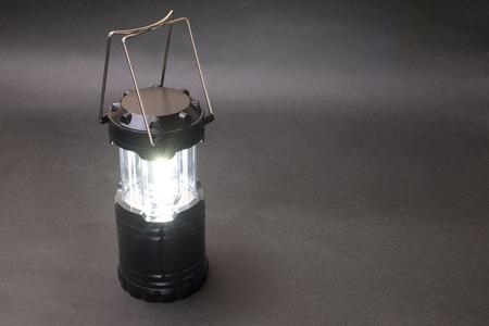 Lighting black LED lantern in front of dark background