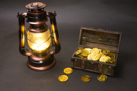 Lighting copper color LED LED lantern and treasure chest with gold coins in front of dark background