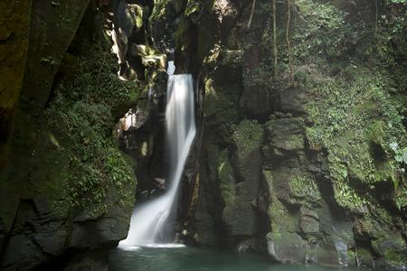 White waterfall falling between green grass grows bedrock in Miyazaki