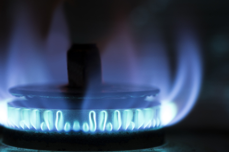 Close up gas stove with blue flame in front of dark background 写真素材