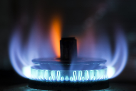 Gas stove with blue and orange flame in front of dark background