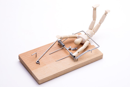 Wooden doll caught in a mouse trap in front of white background 免版税图像