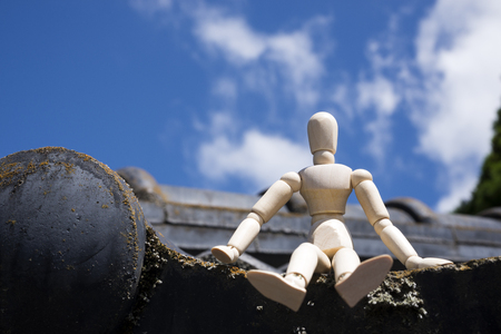 Wooden doll sitting on a asian roof tiles under sky Banco de Imagens
