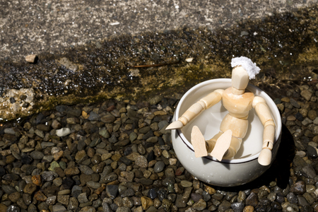 Wooden doll in a pottery tub of spa beside river on gravels