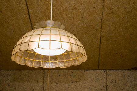 LED pendant light emitting warm color in front of fibrous coating wall Фото со стока