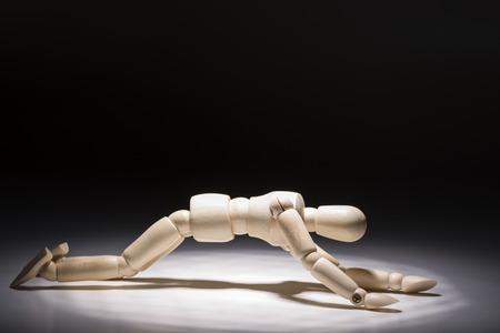 Poupée en bois déprimée à quatre pattes sous un projecteur devant un fond sombre Banque d'images