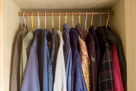 Mehrere Kleidungsstücke aufgereiht im Kleiderschrank getragen Standard-Bild