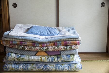 Stacked japanese bedding Futons in front of sliding screen