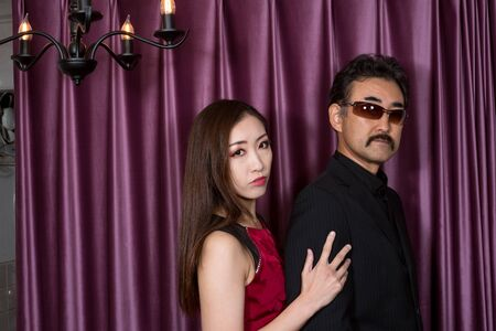 Red dressed woman snuggling up to suited man in front of purple curtain 写真素材
