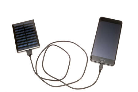 Smartphone charging with solar panel on a white background Archivio Fotografico