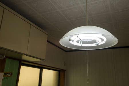 Illuminated fluorescent pendant light hanging in the kitchen