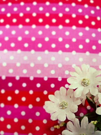 White flowers put on a seamless pattern with with polka dots on a neon pink and red background.