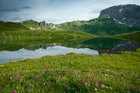 Caucasus mountains and lake with flowers photo