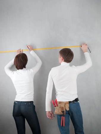 couple measuring wall for home redecorating photo