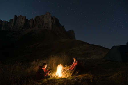 bonfire night: couple tent camping in the wilderness