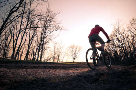 man extreme biking at sunset photo