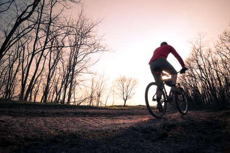 man extreme biking at sunset Stock Photo