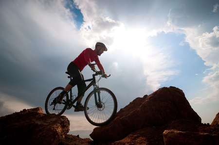 man mountain biking over extreme terrain photo