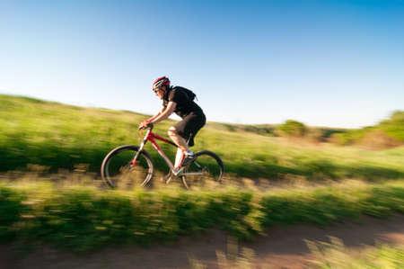 man mountain biking over extreme terrain Stock Photo