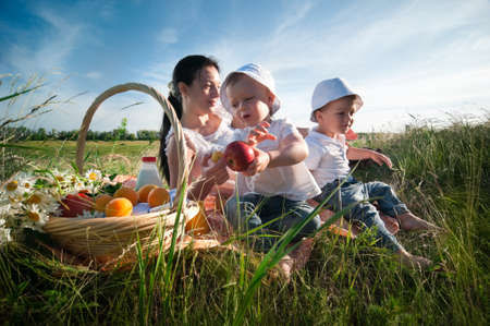 family picnic: madre con hijos con comida campestre