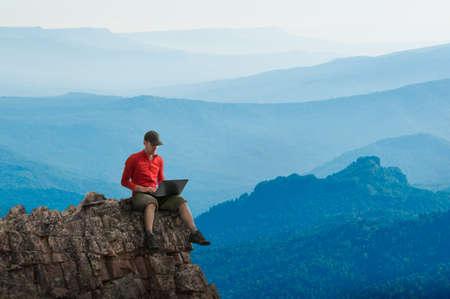 Mann arbeitet im Freien mit Laptop