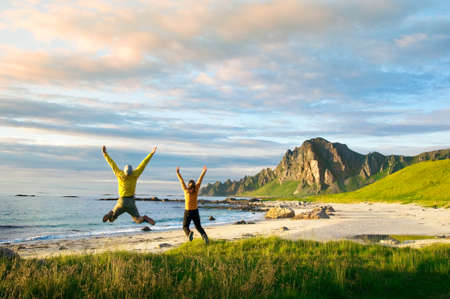 couple jumping on beach in Norway photo