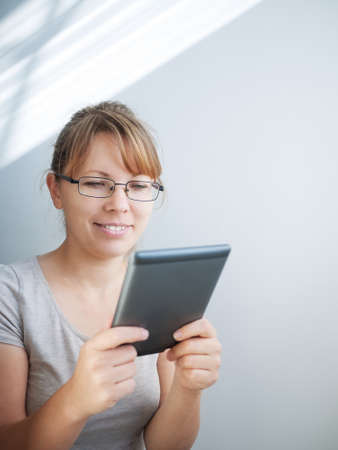 young woman using tablet PC indoors photo