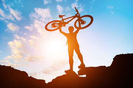 silhouette of man with bicycle at sunset Stock Photo