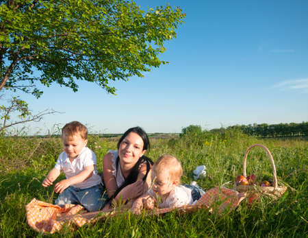 mother with children having picnic photo