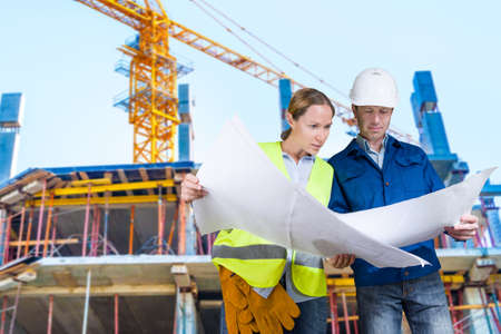 Foreman and engineer with blueprints at construction site photo