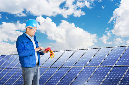 engineer with tablet pc installing solar panels photo