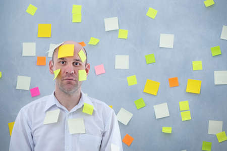 businessman overwhelmed with sticky reminder notes Archivio Fotografico